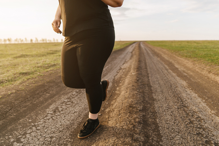 Overweight young woman jogging in the meadow