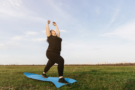 Young woman doing yoga exercises in the meadow Stock Photo