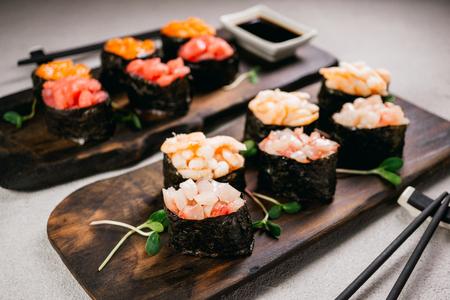 Rouleaux de sushi gunkan maki aux fruits de mer sur plaque de bois