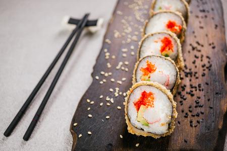 Tempura maki sushi rolls and chopsticks