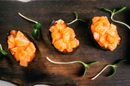 Salmon gunkan maki sushi rolls on wooden plate
