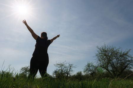 Overweight woman jumping at summer sky background