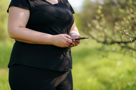 Overweight woman  selecting soundtrack for workout Standard-Bild