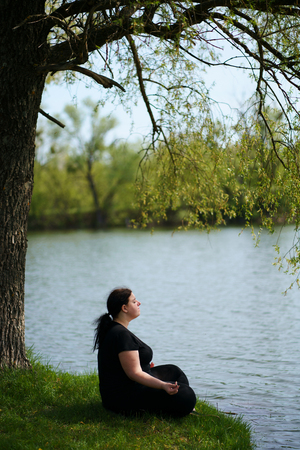 Overweight woman meditating outdoors