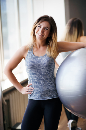 Sporty muscular woman posing with fit-ball