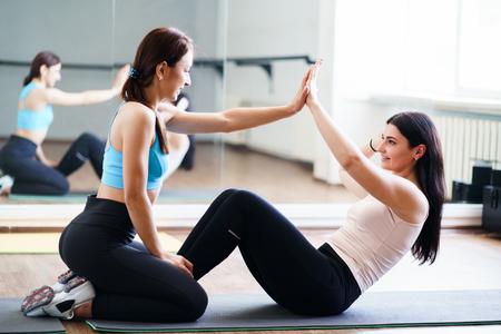 La donna fa gli addominali con il supporto dell'istruttore di fitness