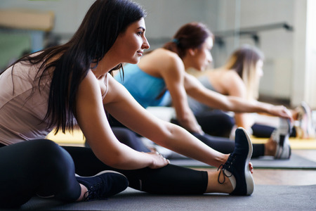 Sporty women stretching during yoga class