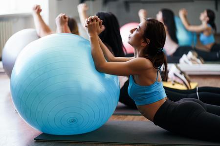 Mujeres haciendo ejercicios de estiramiento en pelotas deportivas Foto de archivo