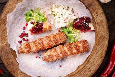 Traditional Adana kebab on wooden plate
