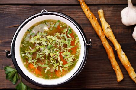 Homemade chicken vegetable soup on a rustic wooden  and bread sticks, healthy tasty nourishing meal