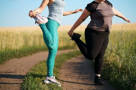 Fit and overweight female friends jogging outdoor