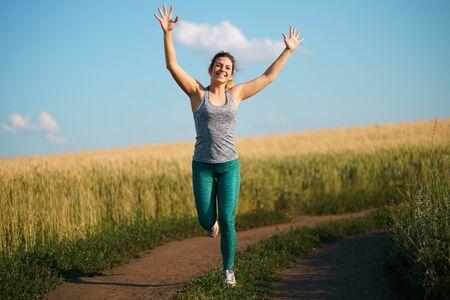 runner raising arms expressing positivity