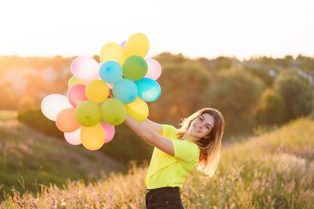 mujer feliz con globos multicolores al atardecer Foto de archivo