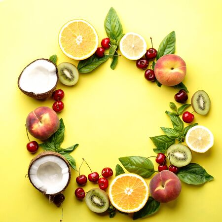Summer vitamin food concept, various fruit and berries. Peach, kiwi, lemon, cherries, oranges and coconut, creative flat lay on yellow background, top view copy space