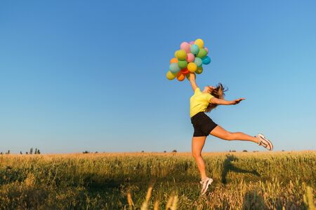 Happy woman jumping with multicolored balloons