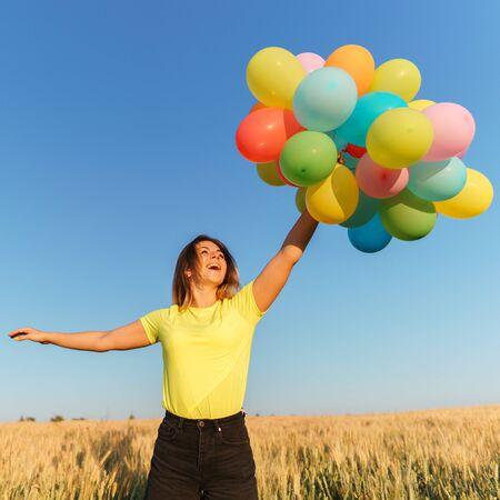 Chica joven con globos de colores en la pradera al atardecer