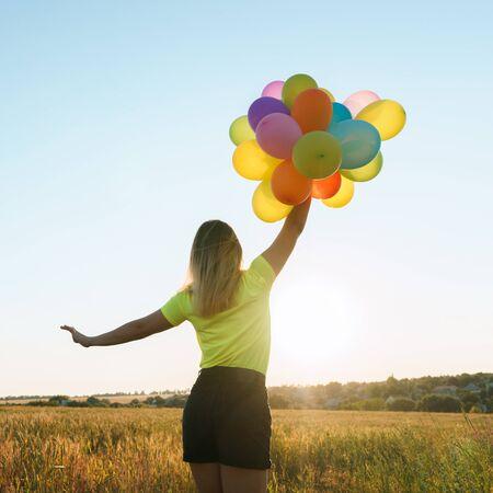 Jonge vrouw met kleurrijke ballonnen in zomer veld Stockfoto