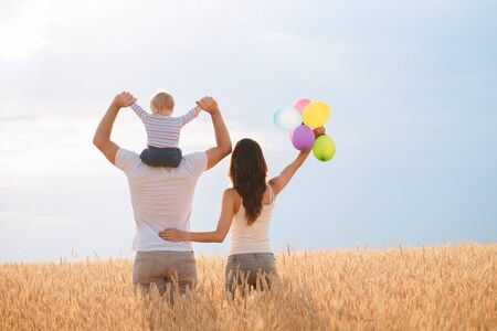 Happy family: mother, father and son on nature