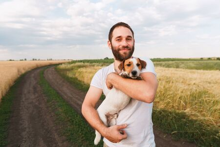 Man playing with his jack russell terrier in field Stok Fotoğraf