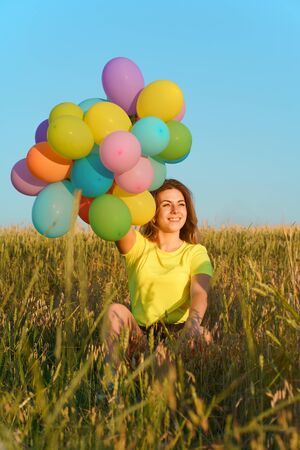 Young girl with colorful balloons in sunset meadow