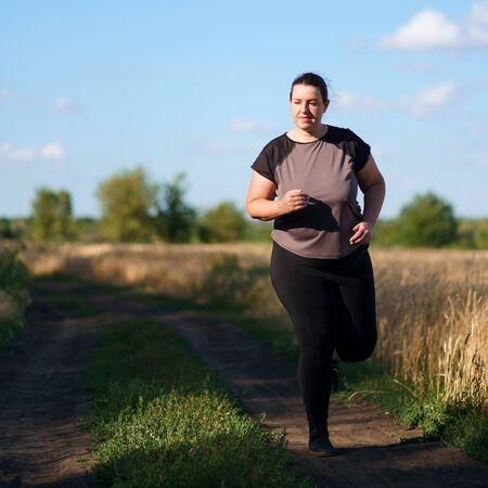 Overweight woman running in countryside Stok Fotoğraf