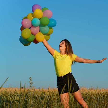 Happy young girl with big bunch of colorful balloons Stok Fotoğraf