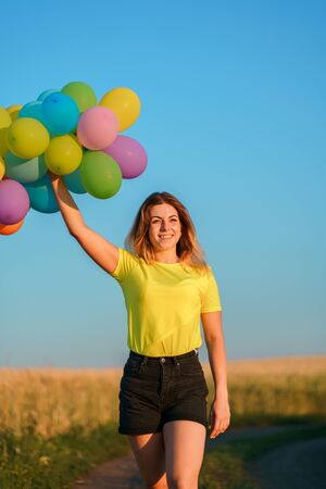 Happy girl with colorful balloons in sunset meadow