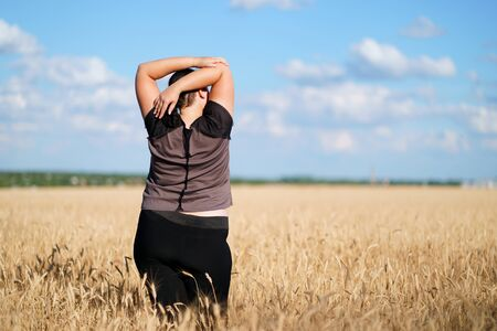 Plus-size woman stretching hands relaxing outdoors Stok Fotoğraf