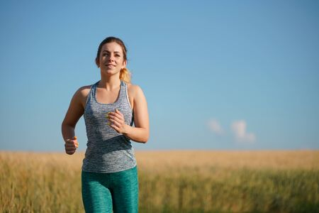 Woman jogger working out in the morning sunny day Stok Fotoğraf