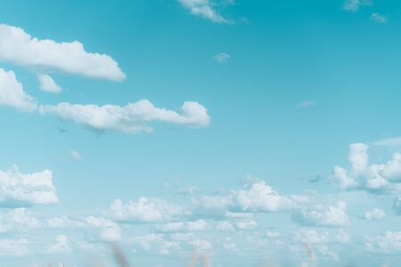 Light blue sky with clouds and sun