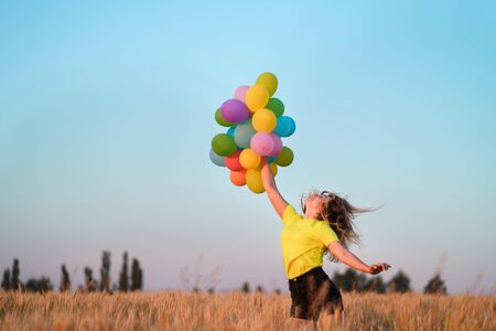 Happy young woman with colorful balloons in summer field