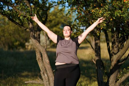 Overweight woman rising hands to the sky Stok Fotoğraf