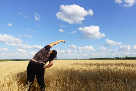 Mujer joven haciendo ejercicios de yoga al aire libre