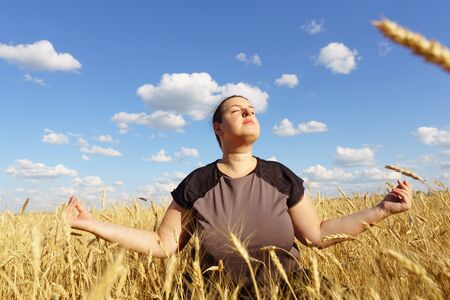 Overweight woman meditating sitting in the field Stok Fotoğraf