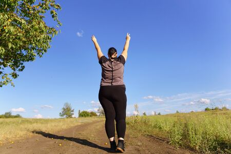 Overweight woman rising hands, view from the back Stok Fotoğraf