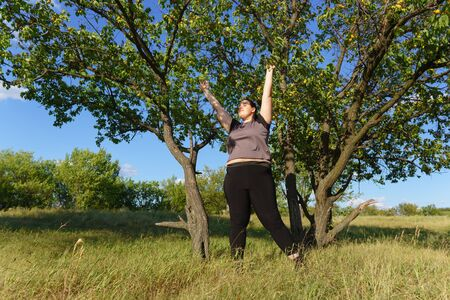 Overweight woman rising hands towards the sky