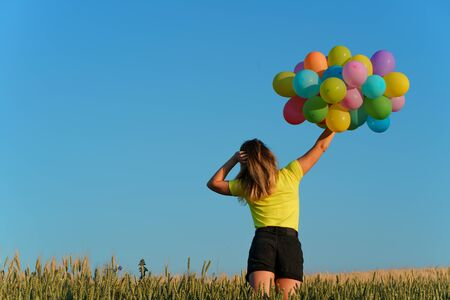 Happy young woman running with balloons on summer field