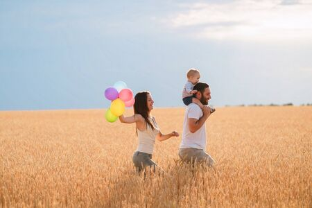 Happy family with bunch of balloons on nature
