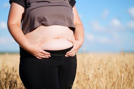 Fat woman in sportswear standing in wheat field