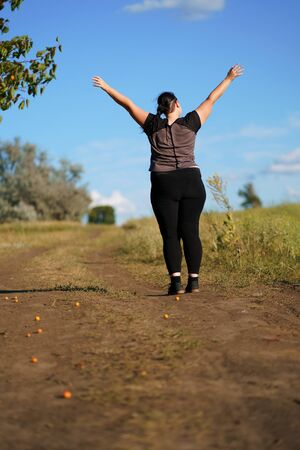 Happy woman standing in nature with open hands. Stok Fotoğraf