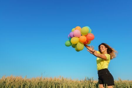 Happy young woman running with multicolored balloons on summer field