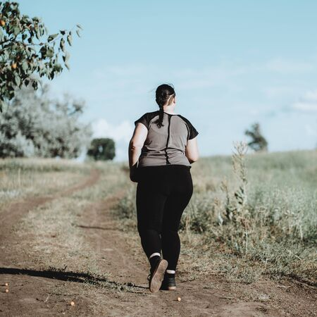 Overweight woman running on summer meadow