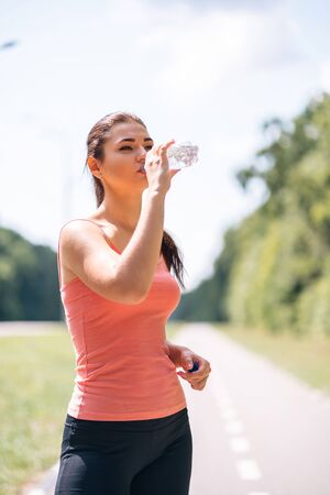 Young fit woman drink water after outdoor jogging