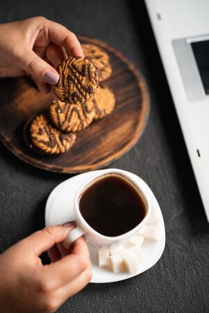 Woman eating cookies and coffee at workplace