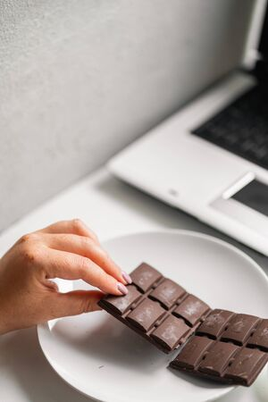 Woman eating chocolate and coffee at workplace Stock Photo