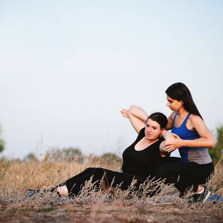 Trainer assisting overweight woman doing sit-ups