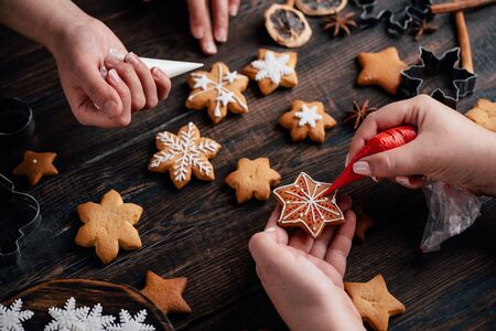 Friends decorating christmas gingerbread cookies