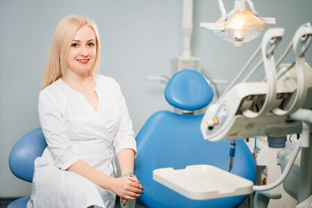 Young woman dentist with dentist chair at the clinic