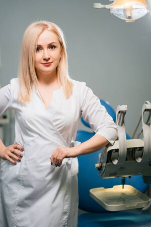 Young woman dentist with dentist chair at the clinic. Imagens