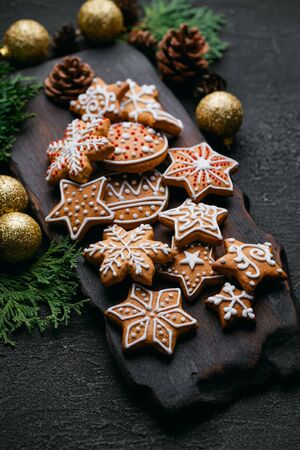 Christmas mood, greeting card background with homemade gingerbread cookies, evergreen branches and decorations on black table. Festive food, New Year celebration traditions Zdjęcie Seryjne